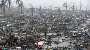 Survivors stand among debris and ruins of houses destroyed after Super Typhoon Haiyan battered Tacloban city in central Philippines
