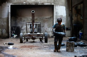 Issa carries a mortar shell in a weapons factory of the Free Syrian Army in Aleppo